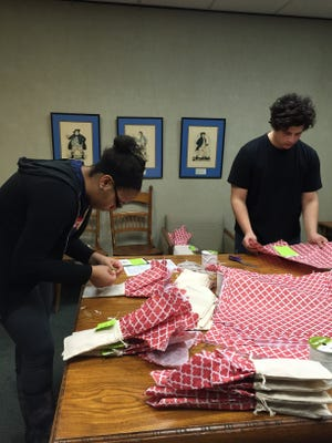 Volunteers wrap certificates showing what donations purchased for charities during the Alternative Gift Fair.