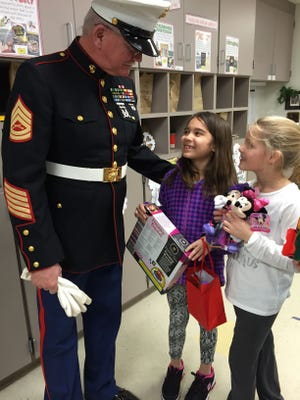 Retired Gunnery Sgt. Frank Gross greets Logen Griffin, center, and classmate Audry Bell. The students are holding some of the toys Logen's classmates donated to Toys for Tots in honor of her father, Randy Griffin, who died in November.