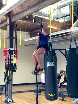Dana Smith climbs a rope as training for a Tough Mudder at Real Life.