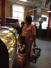 Rochester Mayor Lovely Warren buys a cupcake for daughter Taylor.