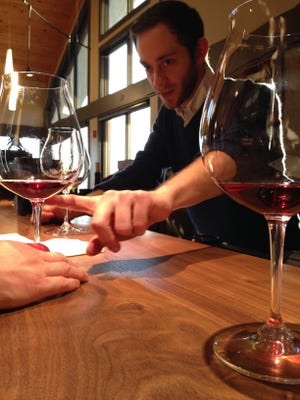 Jacob Sembler, a wine ambassador at Willamette Valley Vineyards, describes one of the many red wines available for tasting.