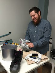 Drew Davis cleans a pair of shoes at Deadstock SBY.