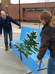 Stevens Point Parks Director Tom Schrader, left, and Grandville, Mich. artist Joe Krajkiewcz install one of four artistic benches on Third Street Friday.
