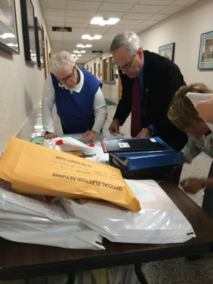 Former mayor Gary Wescott, top right, and other poll workers bring in their ballots to City Hall Tuesday.