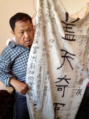 Xie Dezhong, 65, a farmer from southwest China, holds a homemade banner about the death in 2012 of his son Qiang, 22, a case that China's Communist Party-controlled courts refused to handle.