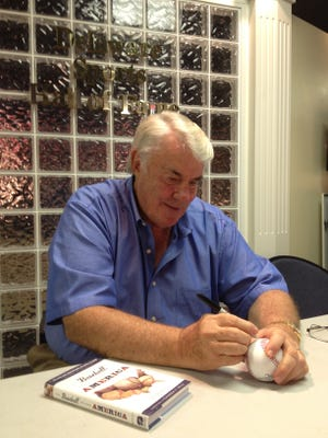 Smyrna native Hal Bodley signs his book and memorabilia before the Blue Rocks game Thursday.