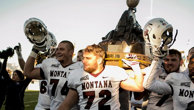 Montana players carry the Great Divide Trophy after defeating Montana State 54-35 in an NCAA college football game in Bozeman Saturday.