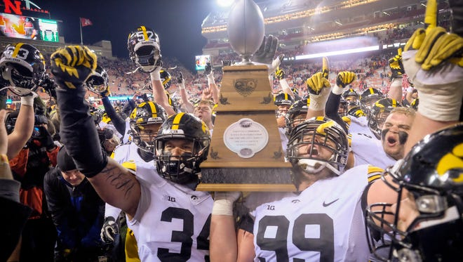 Defensive end Nate Meier and defensive lineman Nathan Bazata and the Iowa Hawkeyes celebrate with The Heros Game Trophy after their game against the Nebraska Cornhuskers at Memorial Stadium November 27, 2015 in Lincoln, Nebraska.