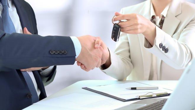 Car salesman handing over the keys/Handshake between two business people. Focus on a key