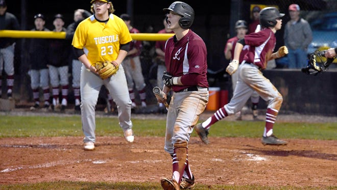 Asheville's Gabe Rentz celebrates during his at bat as teammate Sam Duncan, right, steals home plate on a dropped pitch from Tuscola's Cameron Parker, left, during their game at the Tuscola High School baseball field in Waynesville on Friday, March 30, 2018. The Cougars defeated the Mountaineers 7-5.