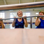 Maxine Bell, 100, does a chin-up at the end of a water aerobics class at the Fort Collins Senior Center last month. Bell, who has been attending the senior center since its opening in 1995, said she chose all new classes to try this year.