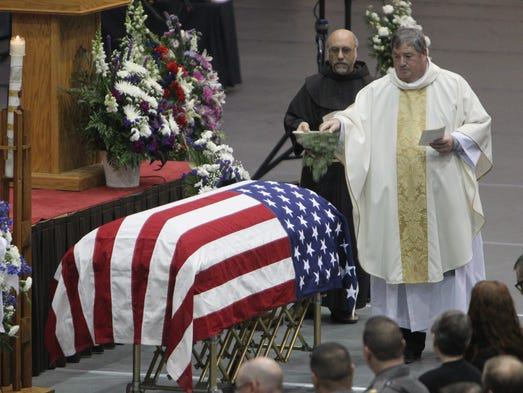 The Reverend Michael Lonto sprinkles holy water over the casket during a funeral Mass for New York State Trooper Ross M. Riley at St. Bonaventure University's Reilly Center in Olean, NY, Tuesday, Nov. 26, 2013. Riley was killed last week in a fall at Letchworth State Park during a training session with the State Operations Response Team.