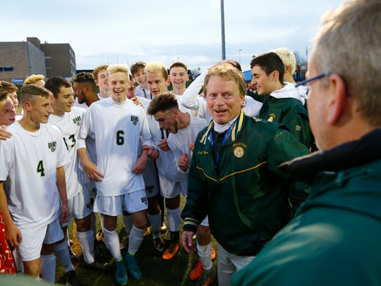 Vestal boys soccer coach, Dave Barr surrounded by his