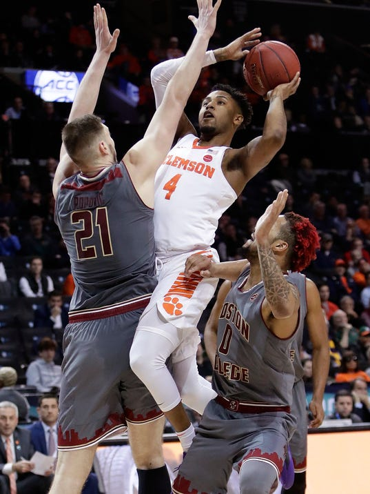 Clemson's Shelton Mitchell (4) shoots over Boston College's Nik Popovic (21) and Ky Bowman (0) during the second half of an NCAA college basketball game in the quarterfinal round of the Atlantic Coast Conference tournament Thursday, March 8, 2018, in New York. Clemson won 90-82. (AP Photo/Frank Franklin II)
