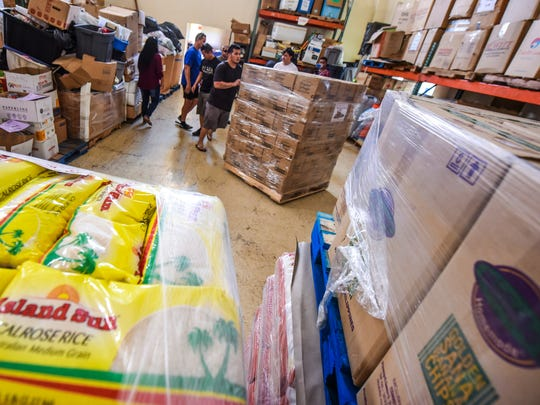 Volunteers cart in another pallet of food, donated by Quality Distributors, to be placed with other items at The Salvation Army's food bank in Tiyan on Tuesday, Nov. 21, 2017. The donation, consisting of rice, luncheon meat, turkeys, ham, cereal and other food items totalling over $31,000, was given to the Salvation Army to help those in the most need on Guam, according to a Quality Distributors release.