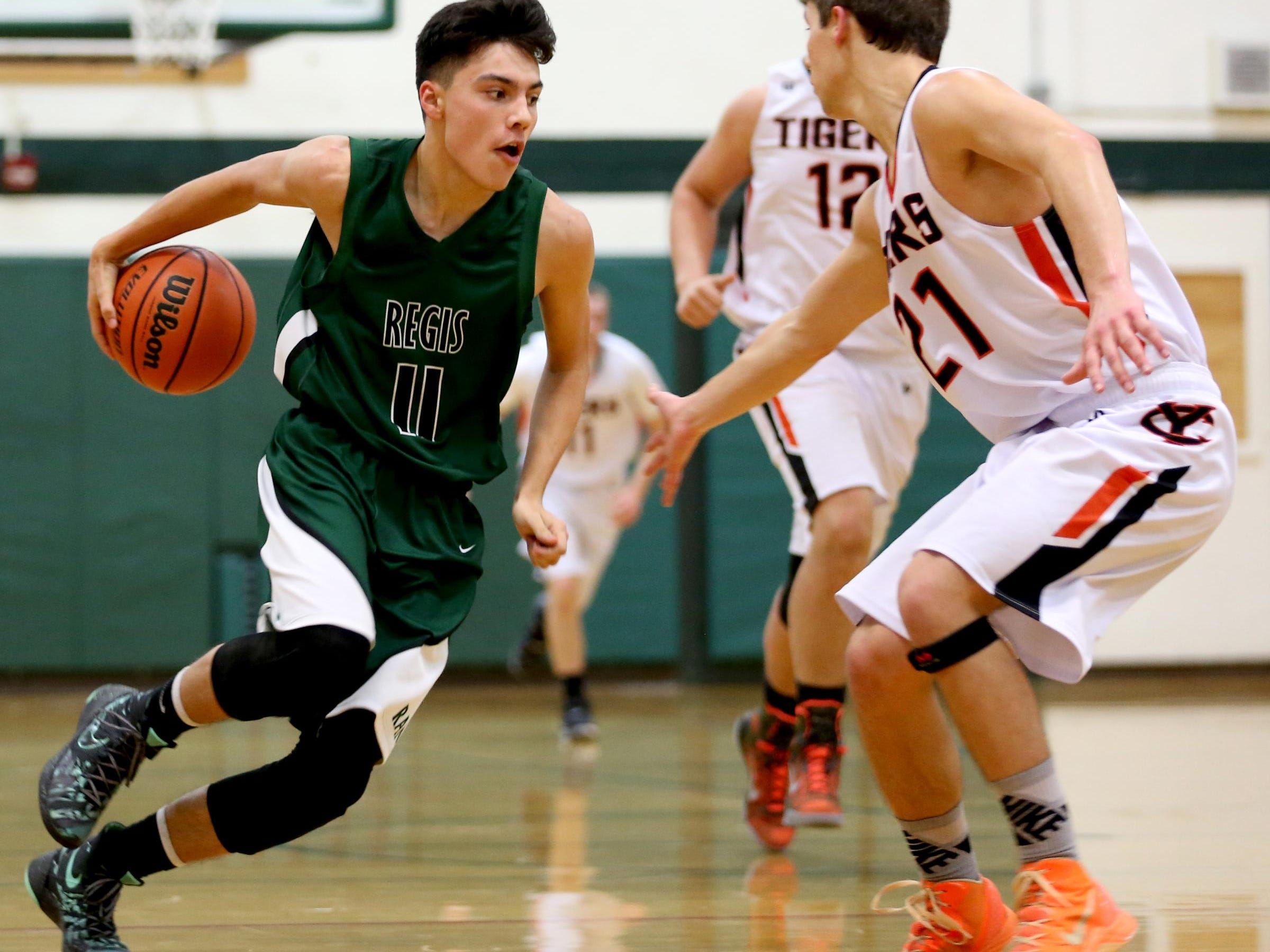 Regis' Brandon Piete (11) moves past Yamhill-Carlton's Luca Quierolo (21) in the second half of the Regis vs. Yamhill-Carlton boy's basketball game in the first round of the North Marion Holiday Classic at North Marion High School in Aurora on Thursday, Dec. 17, 2015. Regis won the game 59-44 and moves on to play in the semifinals at 8 p.m. on Friday.
