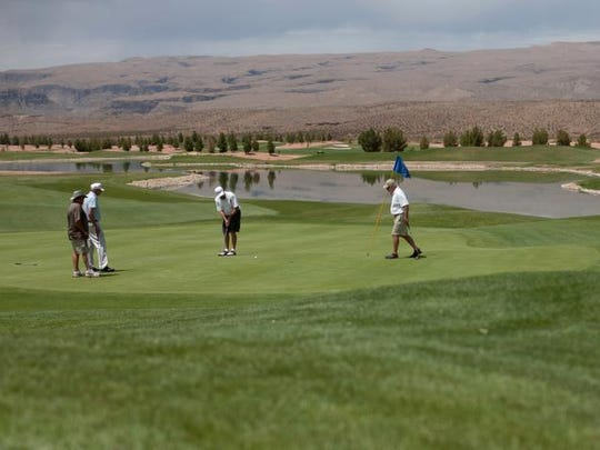 Golfers play the 18th green on the SunRiver Golf Course in July 2012 in St. George.