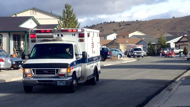 An ambulance drives one of three juveniles to a local hospital in Reno Saturday morning after police responded to a call for medical help at a home in Cold Springs. Washoe County sheriff's deputies were investigating the death of one sibling.