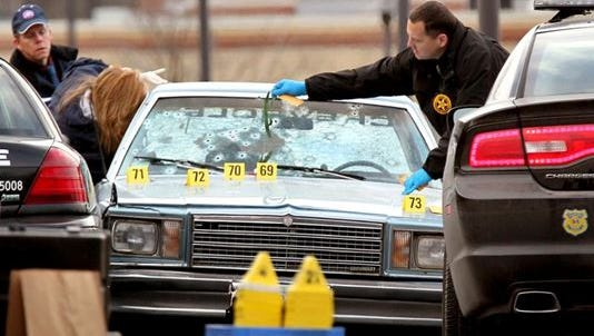Ohio BCI agents and other law enforcement officials investigate a police shooting that killed two people in East Cleveland on Nov. 30, 2012,