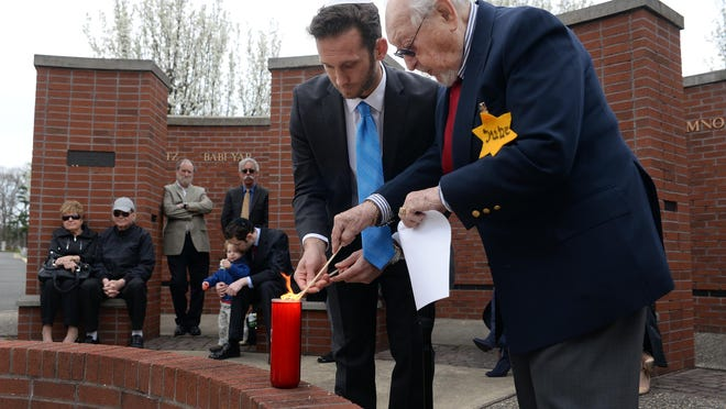 Murray Kohn (right), rabbi emeritus of Beth Israel Congregation, and Steven Schimmel, executive director of the Jewish Federation of Cumberland, Gloucester and Salem Counties, light a candle on Yom HaShoah — or Holocaust Remembrance Day — at the Wall of Remembrance in Alliance Cemetery in Norma.