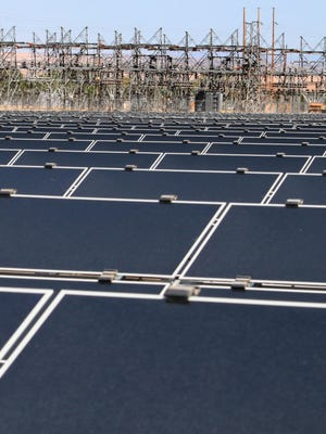 This April 20, 2011 file photo shows dozens of rows of solar panels that make up Public Service Co. of New Mexico's 2-megawatt photovoltaic array in front of transmission lines near the utility's natural gas-fired generating station in Albuquerque. The holding company for New Mexico's largest electric provider has opted to host its annual shareholders' meeting in Texas this year, and on the ballot is a proposal that would require Public Service Co. of New Mexico to adopt goals for reducing greenhouse gas emissions.