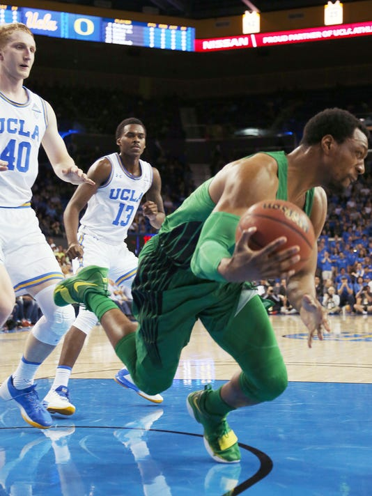 Oregon forward Mikyle McIntosh (22) saves a ball heading out-of-bounds as UCLA guard Kris Wilkes (13) and center Thomas Welsh (40) watch in the first half of an NCAA college basketball game in Los Angeles Saturday, Feb. 17, 2018. (AP Photo/Reed Saxon)