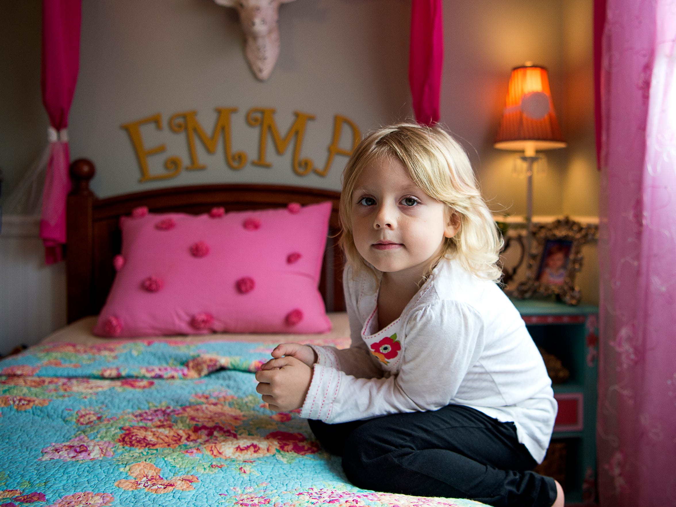 Emma, 6, crouches on her bed in her room in her parents'