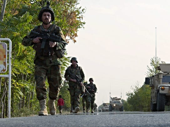 Members of the Afghan National Army secure a road leading