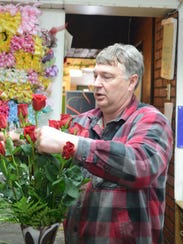 Bob Wistinghausen prepares a bouquet of roses at Wistinghausen