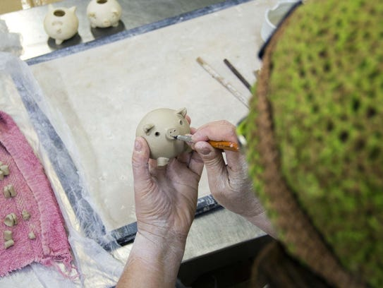 Lori Theriault creates a little pig from clay.