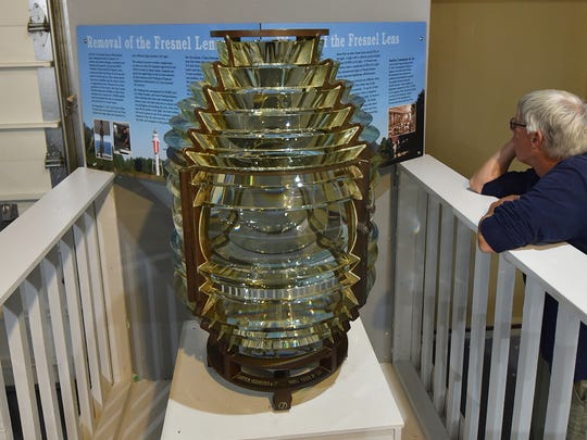 A Fresnel lens fan reads the details of the Plum Island light that was removed and restored by Kurt Fosburg for the U.S. Coast Guard. The lens was constructed in 1889 and served until 2015, when it was replaced with an LED light on the island. The lens is on display at the Door County Maritime Museum's northern museum site in Gills Rock. The lighthouses in Algoma and Kewaunee would also have their Fresnel lenses replaced, according to a proposal from the Boast Guard.