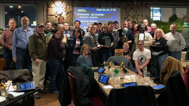 """Members of """"The Fellowship"""" show off some of their awards at a gathering at the  Red Fox Sports Pub & Grille in Cuyahoga Falls in 2019. The group has been voted into the international Trivia Hall of Fame."""