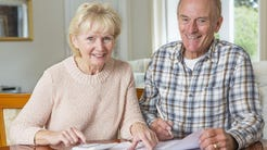 An elderly couple reviewing their finances.