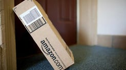 An Amazon package laid against a door for delivery.