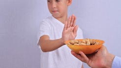 A child sticking their hand out to refuse a bowl of peanuts.
