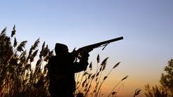 A silhouette of a hunter in a field aiming their gun.