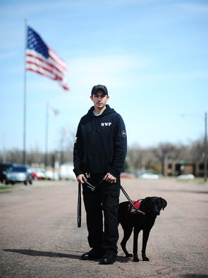 Robert Solorzane, a retired Army Ranger, poses for a portrait on Thursday, April 17, 2014, with his Big Paws Canine service dog, Huey, outside of ABN Army Surplus, where Solorzane works, in Sioux Falls. (Joe Ahlquist / Argus Leader)