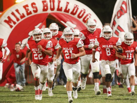 The Miles Bulldogs charge onto the field before their
