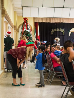 A volunteer helps out during the annual Christmas party for economically challenged families in Fort Myers, on Saturday, Dec. 16, 2017.