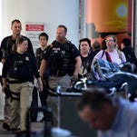 Armed officers patrol the international arrivals section at Los Angeles International Airport after Brussels bombings, March 22, 2016.