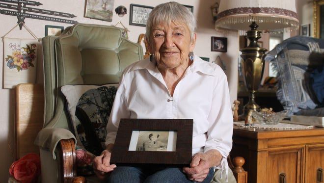 Second World War veteran Bonnie Stage sits with a photo of herself as a nursing assistant in 1945 at her home Tuesday afternoon.