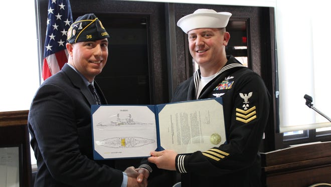 Social Studies instructor and U.S. Army veteran Ed M. Graf (left) and U.S. Navy machinist mate 1st Class Larsen pose with the documentation for the relic of the USS Arizona.