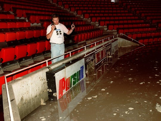 Andy Long, a marketing official at the Iowa State Center, stood flood watch behind the basketball scoreboard at Hilton Coliseum on Saturday, July 10, 1993, where water rose 14 feet above floor level Friday, July 9.