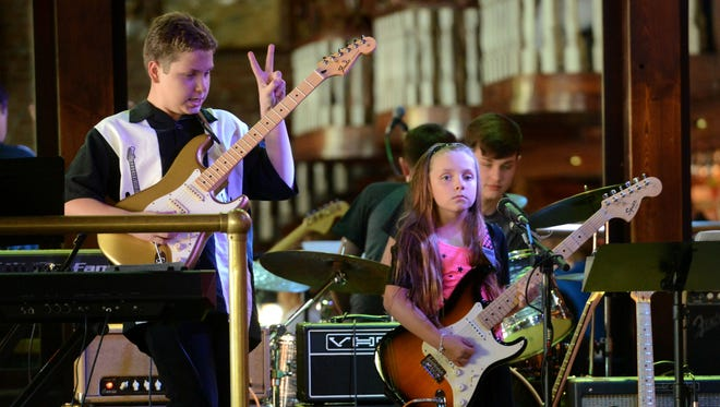"""Music students Ethan Peeler, 12, and Kaelyn Peeler, 9, and Ethan Mosley, drums, perform """"Mary Had a Little Lamb"""" by Stevie Ray Vaughn on Wednesday at Seville Quarter during the Gulf Coast School of Music Spring 2014 Student Show."""