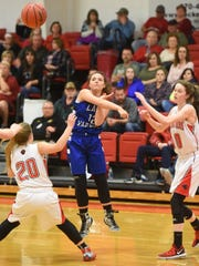 Cotter's Macie Clawson throws a pass out of the trap of Norfork's Matty Dillard (20) and Marleigh Dodson on Tuesday night.
