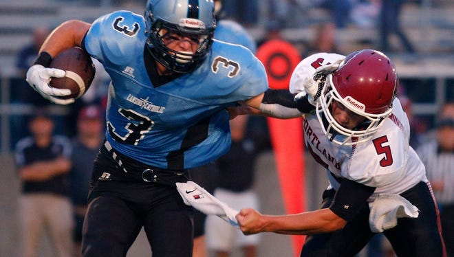 Portland's Cole McGregor, right, attempts to tackle Lansing Catholic's Tony Palmer, left, last season. McGregor, now a senior, is the leading tackler for the Raiders.
