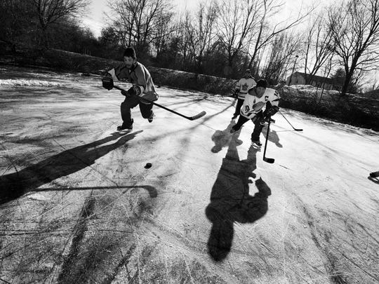 "A photo by Nicholas Wynia shows a game of pond hockey. The photo is apart of the new book ""Pond Hockey: Frozen Moments."""