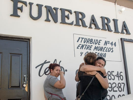 Selene Ramirez (right) consoles her sister, Reyna Martinez, outside the funeral home in Sonoyta, Mexico, after they arrived to reclaim the body of their brother Carlos Martinez.
