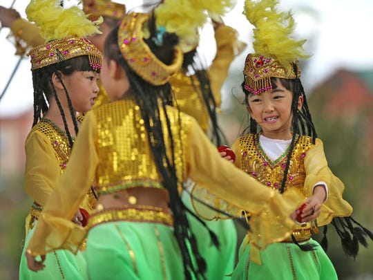 Yaya Wang smiles as she performs with friends during the Indianapolis Chinese Festival.
