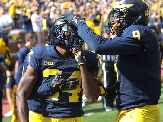 Michigan's Lavert Hill is congratulated by teammates